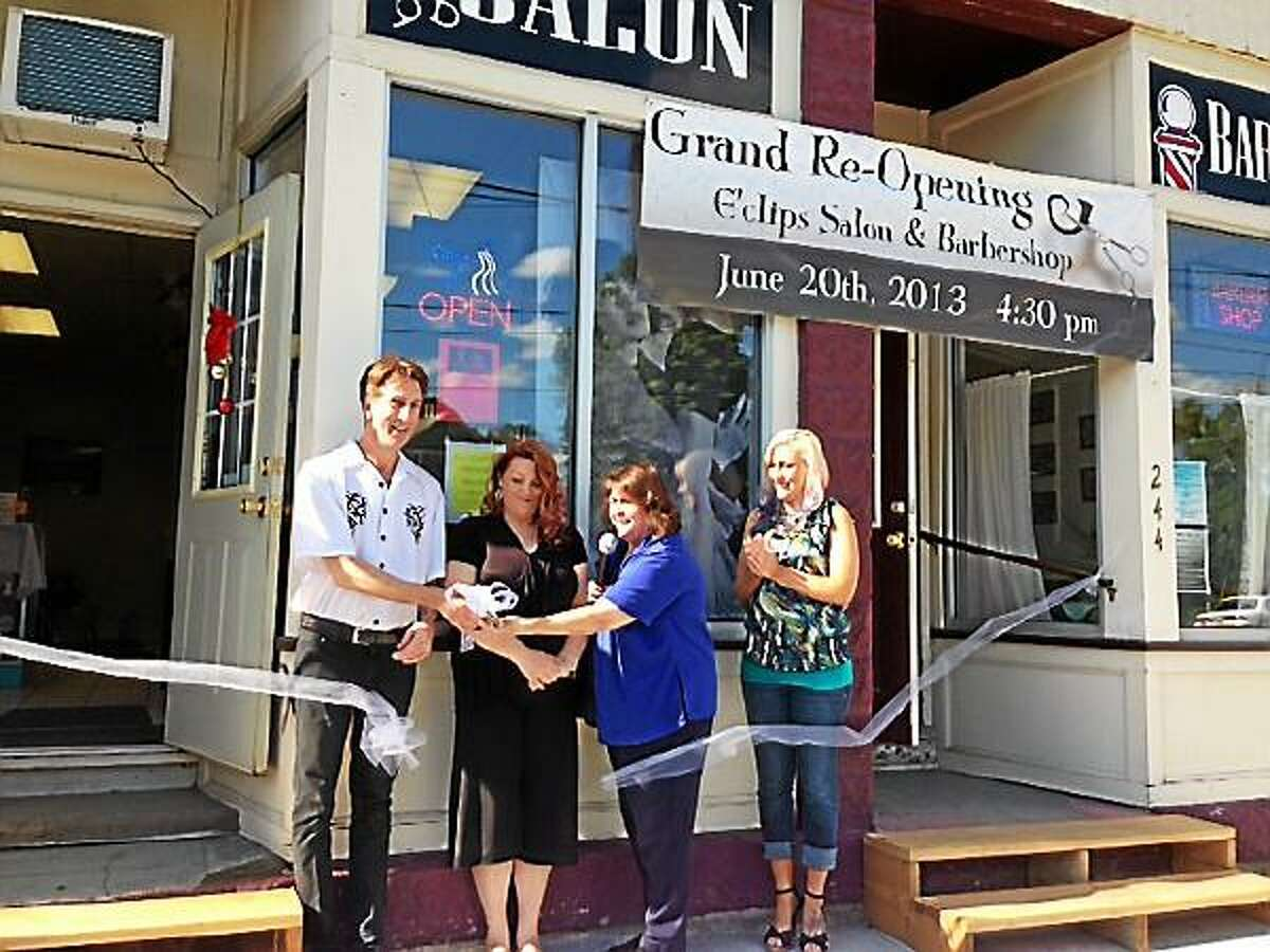E'Clips staff cut the ribbon for its grand re-opening with Mayor Maryann Welcome. Mercy Quaye -- Register Citizen.