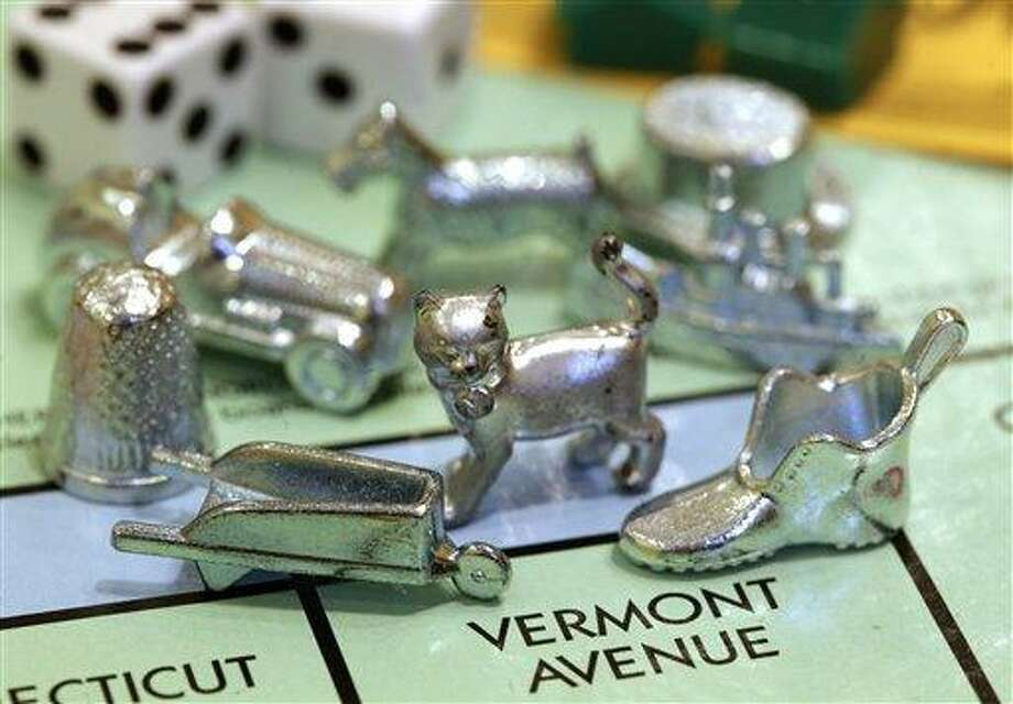 The newest Monopoly token, a cat, center, rests on a Boardwalk deed next to other tokens still in use including the wheelbarrow, left, and the shoe, right, at Hasbro Inc. headquarters, in Pawtucket, R.I., Tuesday, Feb. 5, 2013.  Voting on Facebook determined that the cat would replace the iron token.  (AP Photo/Steven Senne) Photo: ASSOCIATED PRESS / AP2013