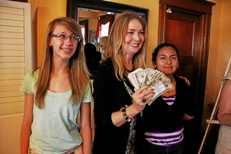 From left: Corina Wallenta, Teresa Sullivan and Leslie Tapia-Bernal smile as they celebrate winning the first ever Torrington Dough on Thursday, June 20, 2013. Teresa Sullivan is holding the prize money, $560, which she won after a short pitch.  Esteban L. Hernandez - Register Citizen