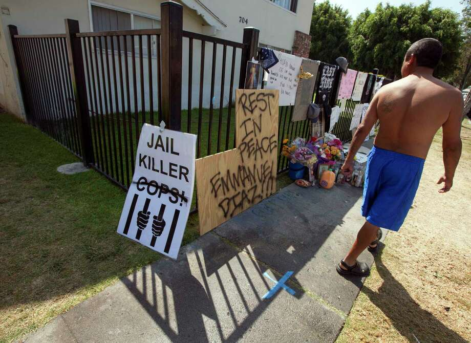 A neighbor walks past a memorial for police shooting victim Manuel Angel Diaz, 25, in Anaheim, Calif., in 2012. Diaz was shot and killed by Anaheim police. Photo: Associated Press  / AP