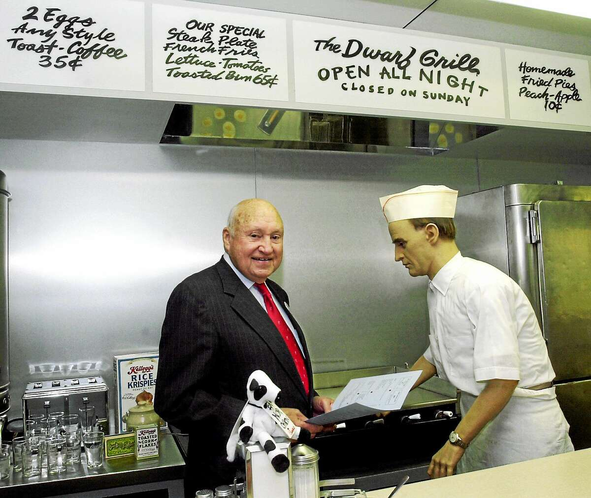 """In this November 2001 file photo, S. Truett Cathy, founder of Chick-fil-A, poses in a replica of """"The Dwarf Grill,"""" the original restaurant he started in Atlanta in 1946. A spokesman said Cathy, who started the postwar diner in Atlanta that grew into the Chick-fil-A restaurant chain, died early Monday."""