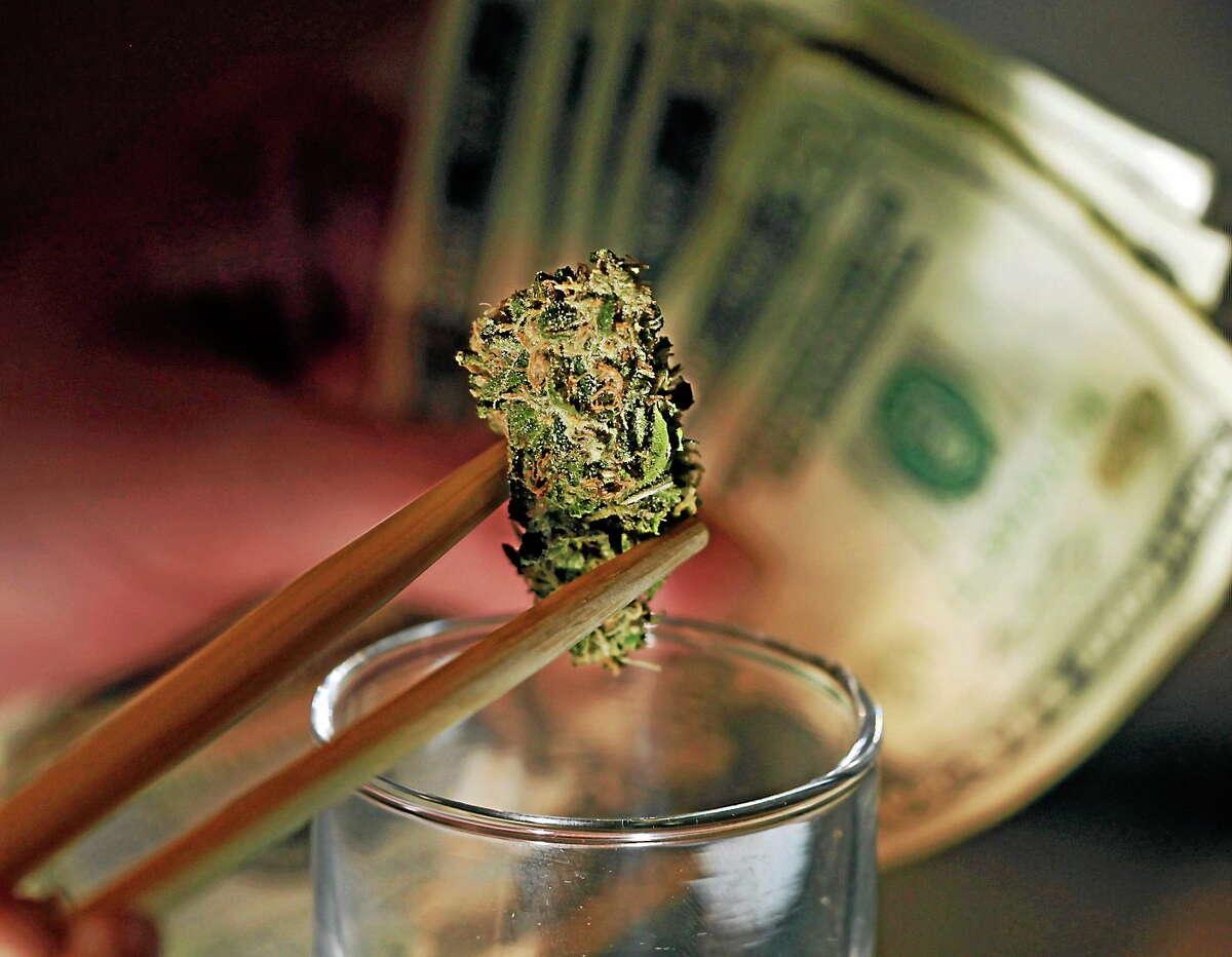 A caregiver picks out a marijuana bud for a patient at a marijuana dispensary in Denver.