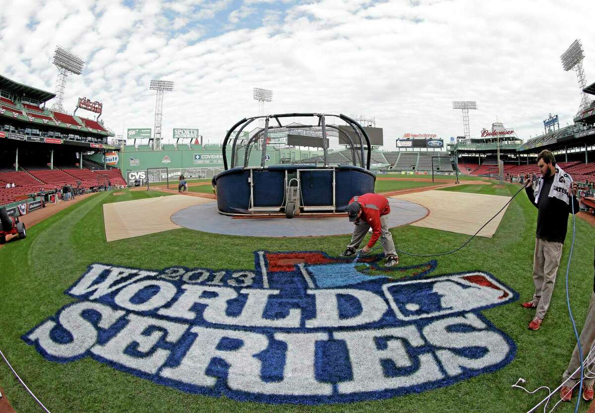 Chris Williams paints a logo on the field at Boston's Fenway Park Tuesday in anticipation of the World Series, which begins on Wednesday.