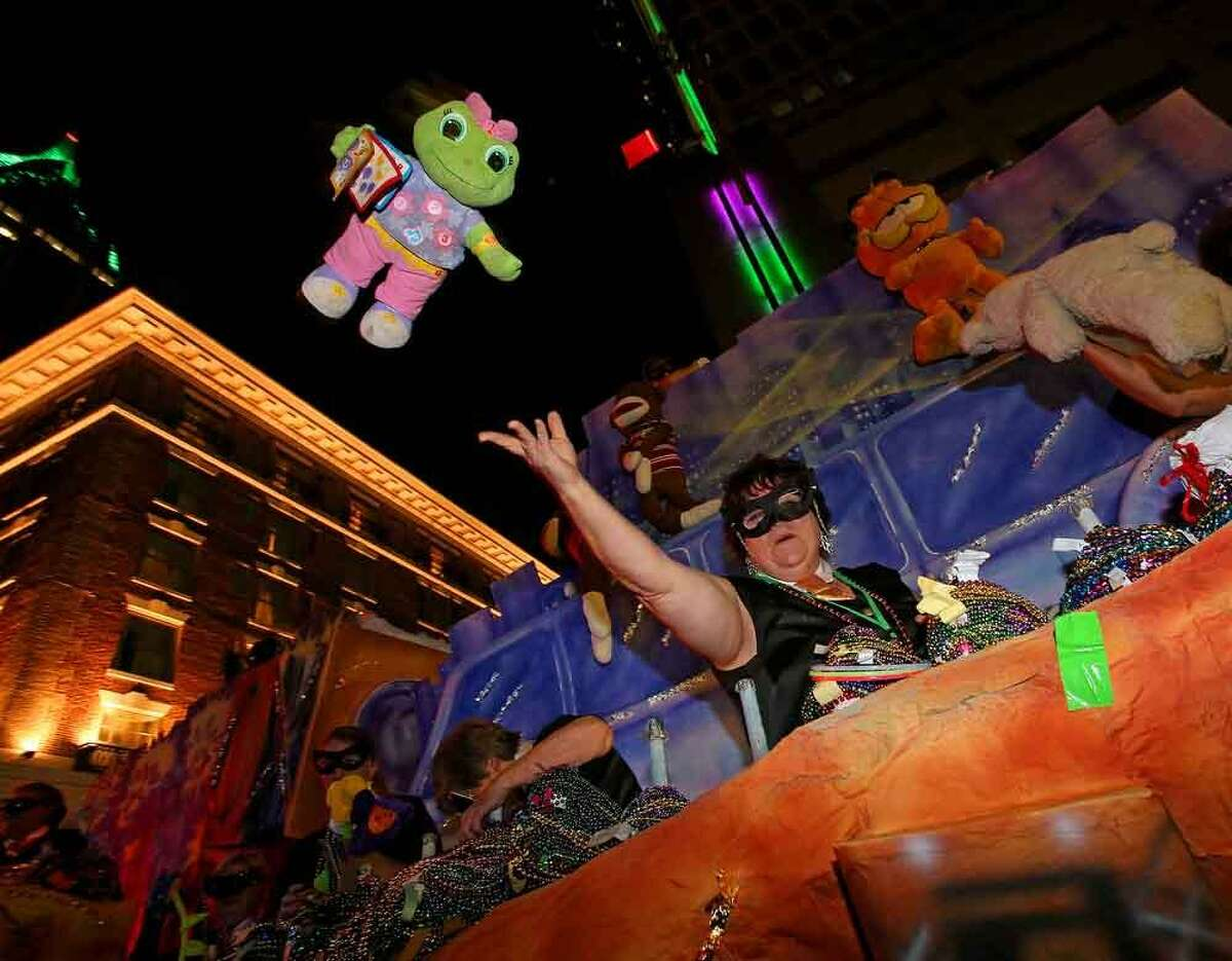 A Member of the Order of LaShe's throws a stuffed animal to the crowd during their Mardi Gras parade downtown Mobile, Ala., Tuesday, Feb. 5, 2013. (AP Photo/Al.com, Bill Starling)