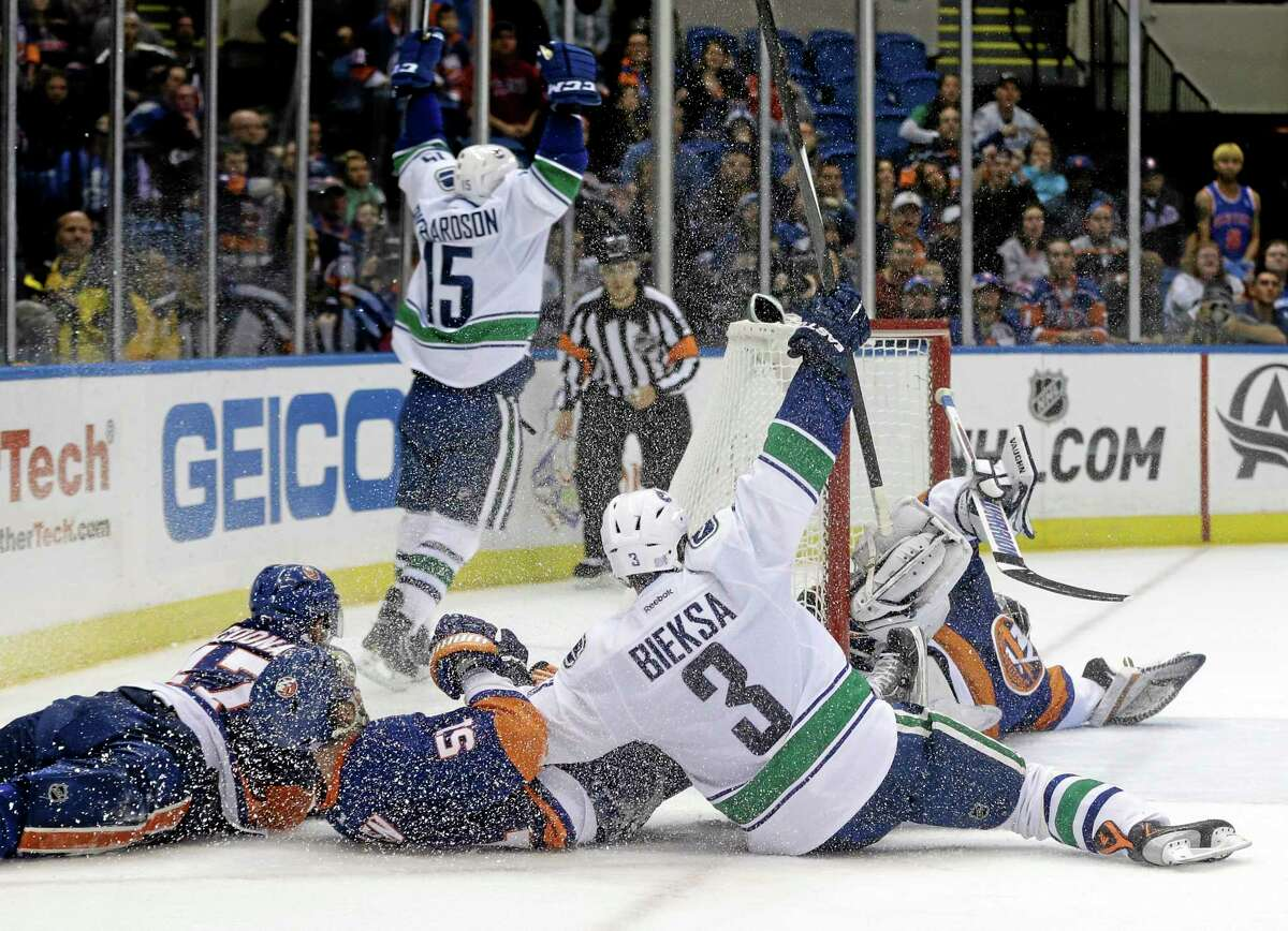 The Vancouver Canucks' Brad Richardson (15) and Kevin Bieksa celebrate after Richardson scored during overtime Tuesday night against the Islanders in Uniondale, N.Y. The Canucks won the game 5-4.