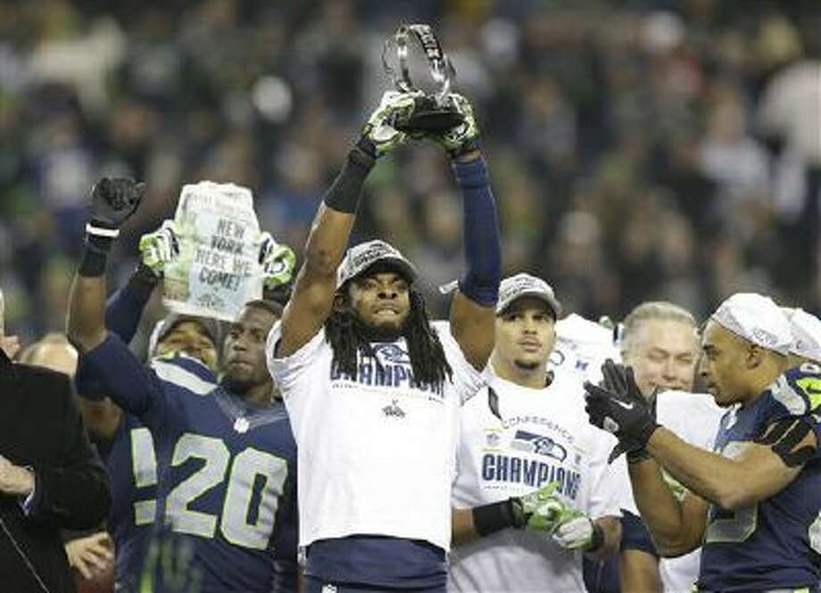 Seattle Seahawks' Richard Sherman holds up the George Halas Trophy after the NFL football NFC Championship game against the San Francisco 49ers Sunday, Jan. 19, 2014, in Seattle. The Seahawks won 23-17 to advance to Super Bowl XLVIII. (AP Photo/Elaine Thompson) Photo: AP / AP
