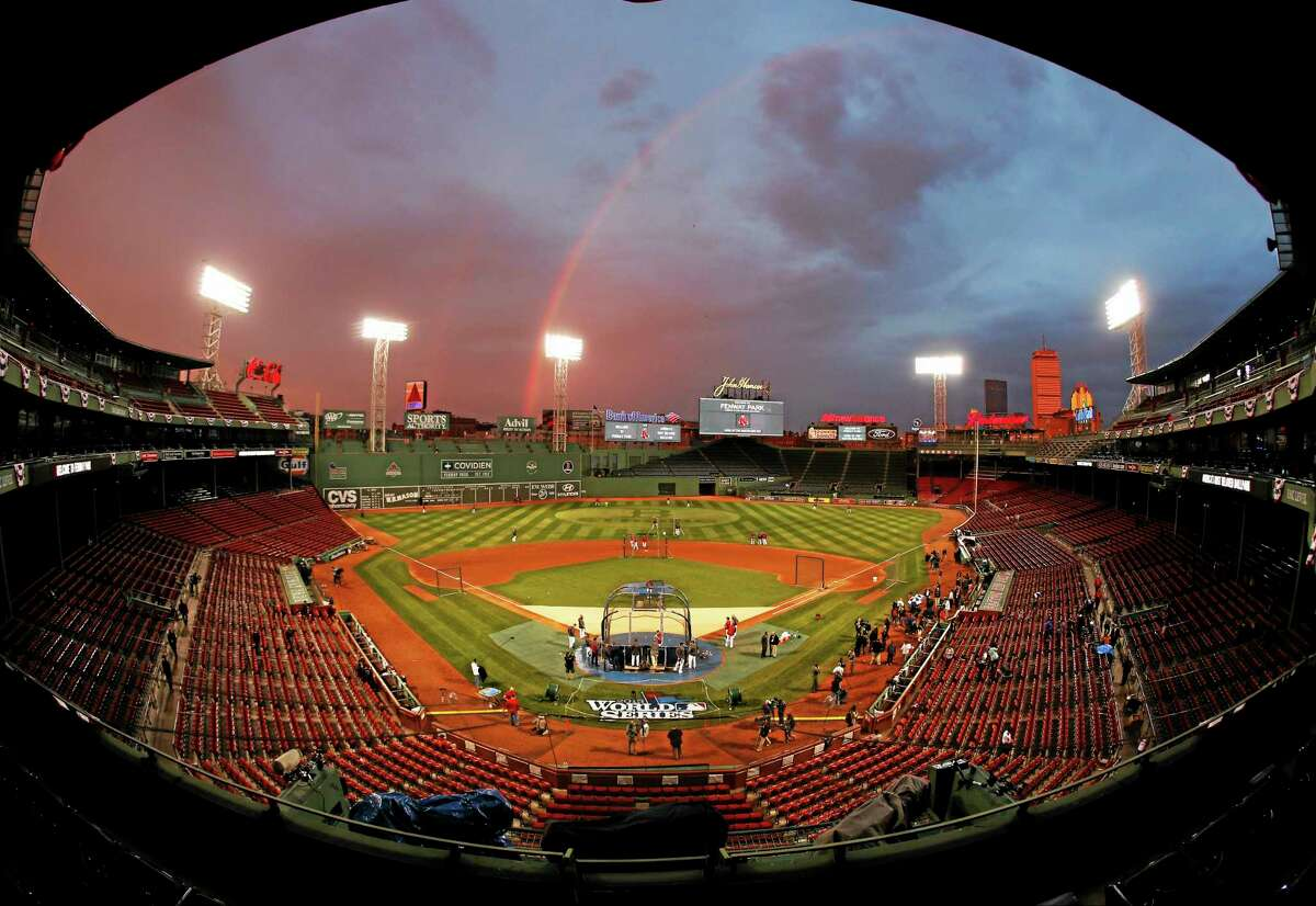 In this image taken with a fisheye lens, Red Sox players take batting practice as a rainbow appears in the sky above Fenway Park on Tuesday in Boston. The Red Sox will host the St. Louis Cardinals in Game 1 of the World Series on Wednesday.
