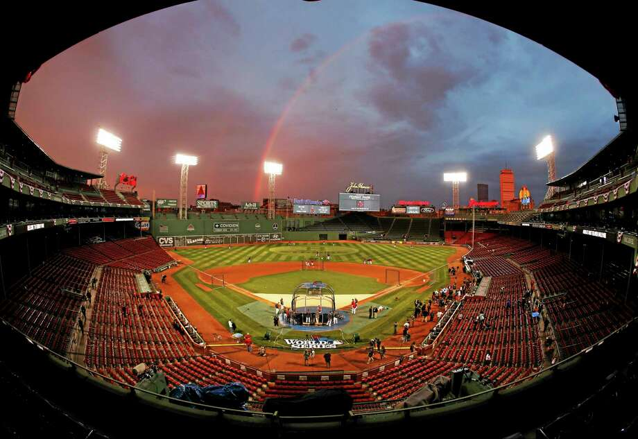 In this image taken with a fisheye lens, Red Sox players take batting practice as a rainbow appears in the sky above Fenway Park on Tuesday in Boston. The Red Sox will host the St. Louis Cardinals in Game 1 of the World Series on Wednesday. Photo: Elise Amendola — The Associated Press  / AP