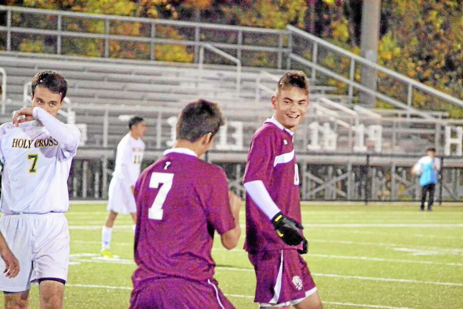 Torrington's Shane Bierfeldt celebrates with teammates Amar Suljic after scoring the first goal in the Red Raiders 3-0 win over Holy Cross. Photo: Pete Paguaga — Register Citizen