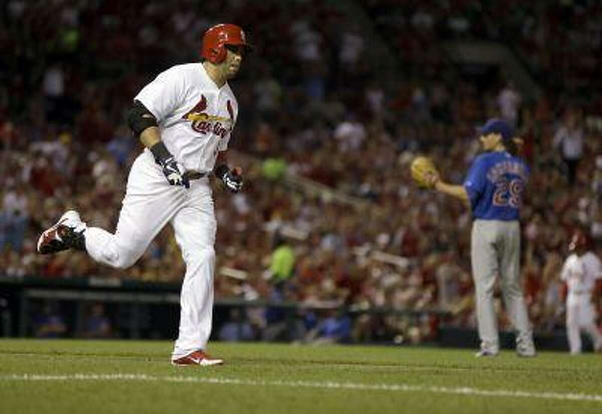 St. Louis Cardinals' Carlos Beltran, left, rounds the bases after hitting a solo home run off Chicago Cubs starting pitcher Jeff Samardzija, right, during the sixth inning of a baseball game on Tuesday, June 18, 2013, in St. Louis.