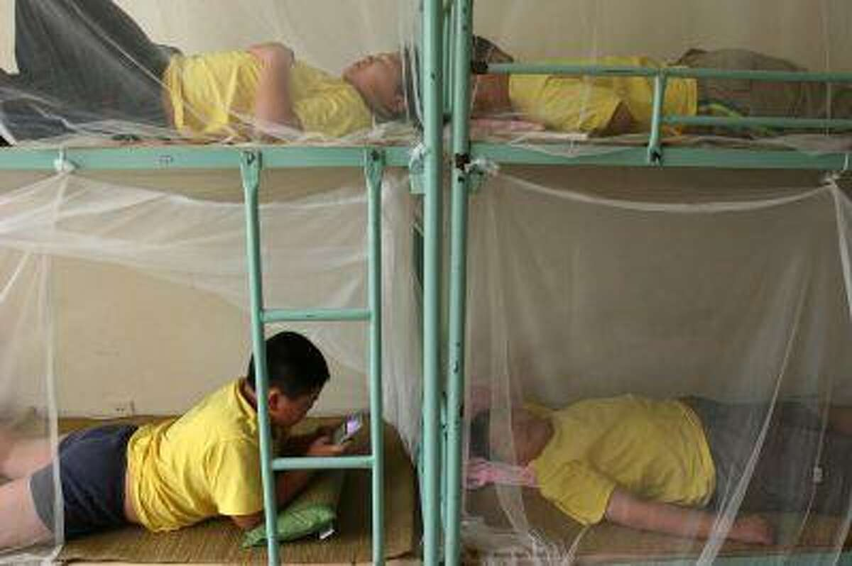 Children rest during a weight-losing summer camp organized by a slimming centre in Wuhan, central China's province July 13, 2006. CHINA OUT REUTERS/Stringer