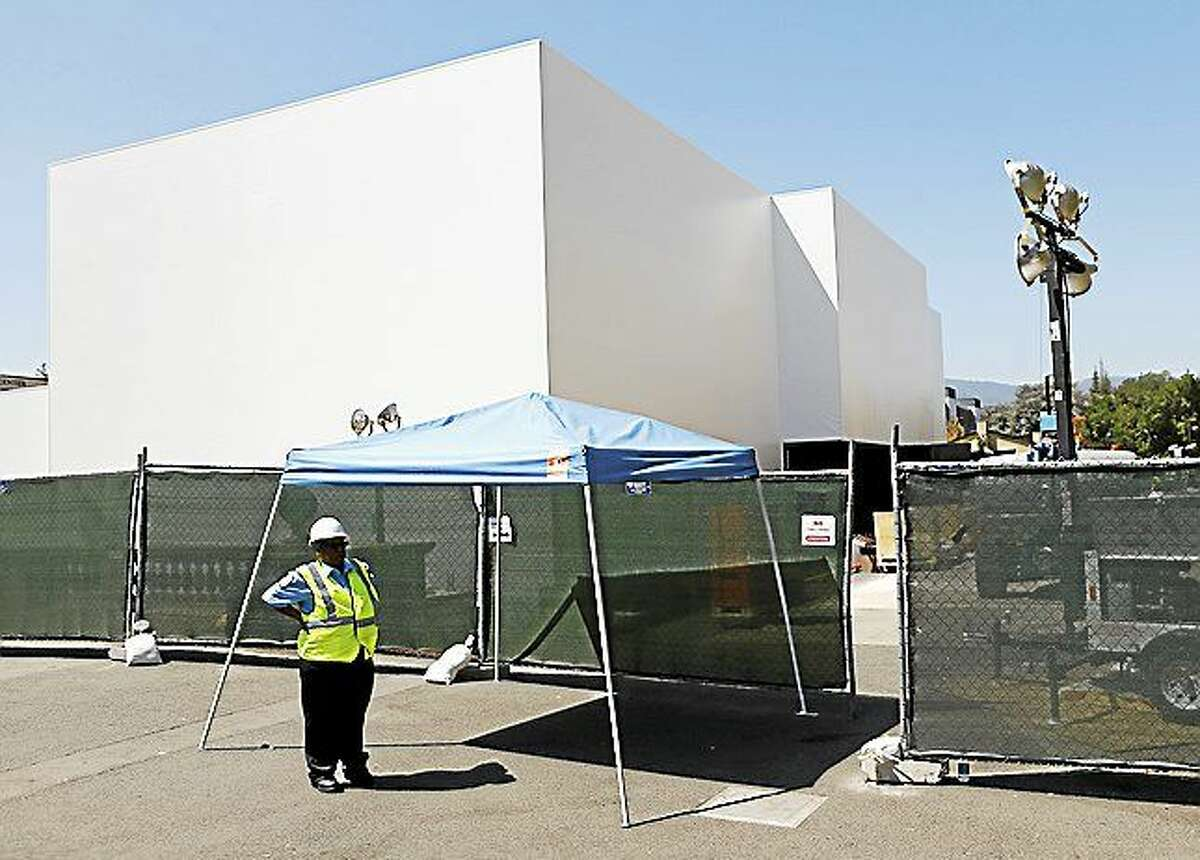 A security guard protects the entrance of an unidentified Apple building under construction next to the Flint Center on the De Anza College campus in Cupertino, Calif., on Aug. 28, 2014.