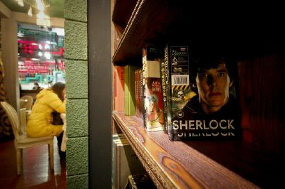 "A girl has a drink at a ""Sherlock""-themed cafe in Shanghai, China."