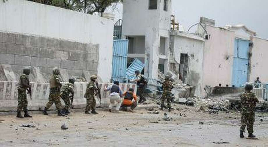 African Union peacekeepers and unidentified foreigners stand outside the main U.N. compound, following an attack on it in Mogadishu, Somalia Wednesday, June 19, 2013. Photo: ASSOCIATED PRESS / AP2013