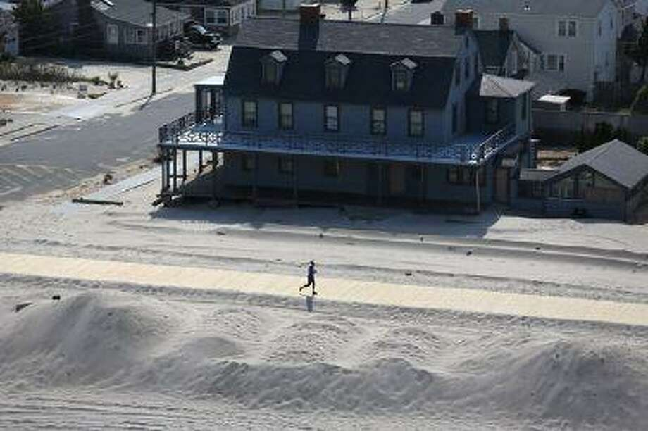 A resident jogs along a new stretch of boardwalk and restored beach more than six months after Superstorm Sandy in May 2013 in New Jersey. (John Moore/Getty Images) / 2013 Getty Images