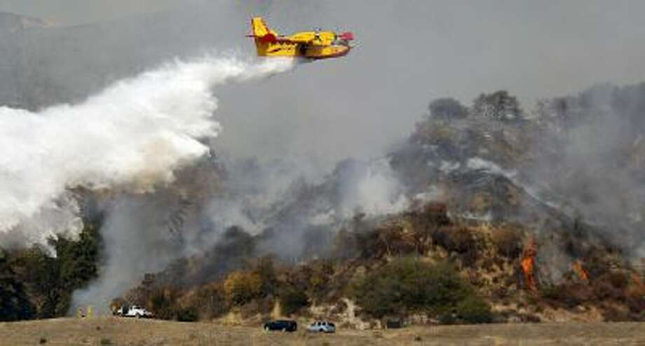 A firefighting plane makes a water drop on a wildfire that's burning in the hills just north of the San Gabriel Valley community of Glendora, Calif., on Thursday, Jan 16, 2014.