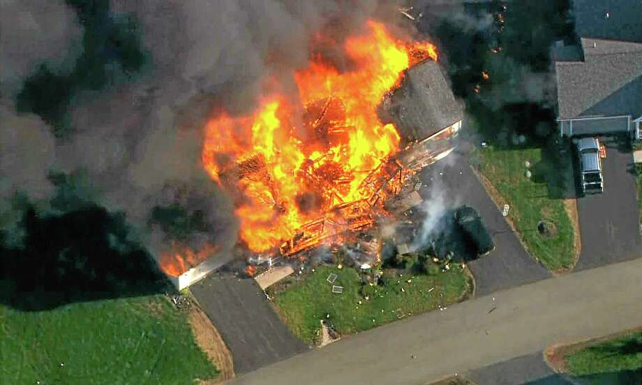 In this frame grab from television helicopter video, a home bursts into flames in Brentwood, N.H., Monday May 12, 2014.  Shots were fired just before the fire, which involved a police officer, according to the New Hampshire State Police. (AP Photo/WCVB-TV 5) TV OUT Photo: AP / WCVB-TV 5