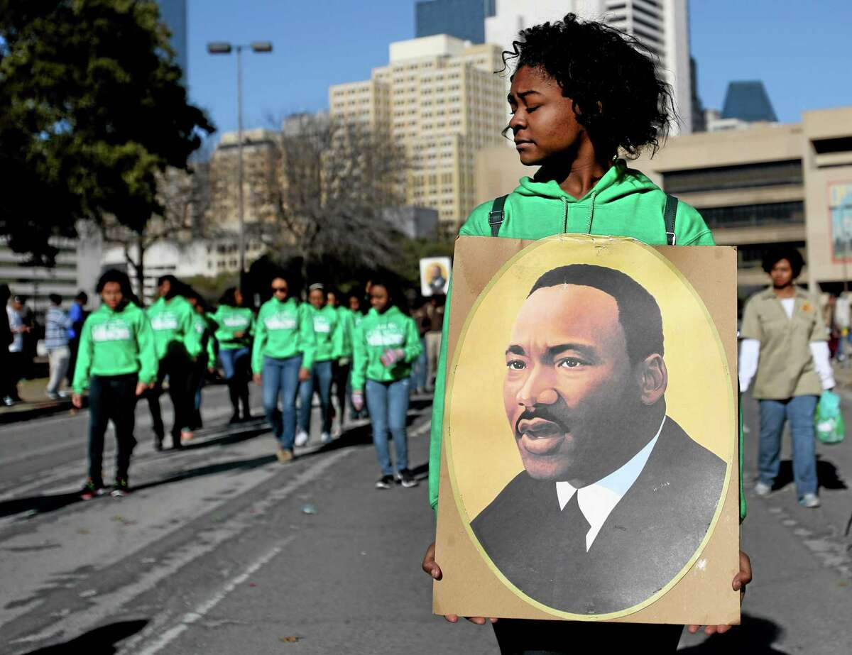 Sakidra Davis of Alpha Rho Xinos carries an image of Martin Luther King Jr. during the 32nd annual Martin Luther King Jr. Birthday Celebration's March/Parade on Saturday Jan. 18, 2014, in Dallas, Texas. (AP Photo/The Dallas Morning News, Sarah Hoffman) MANDATORY CREDIT