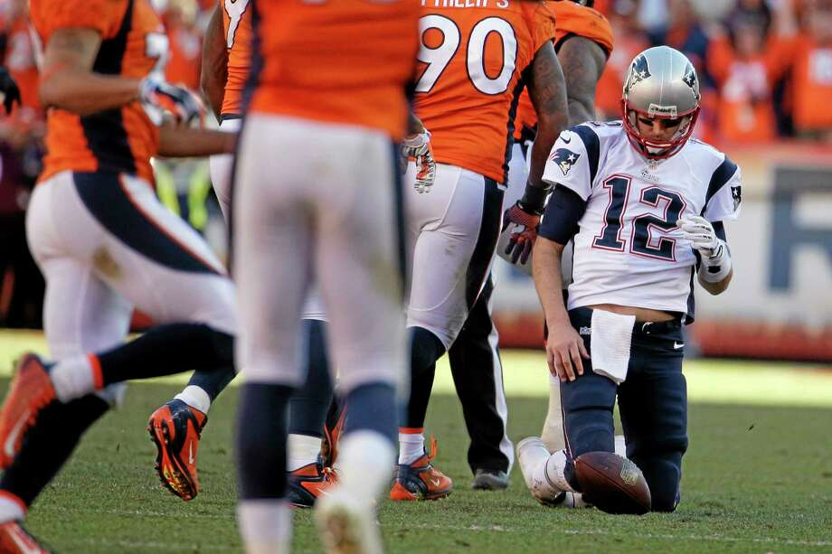 Patriots quarterback Tom Brady (12) remains on his knees after being sacked during the second half of the AFC Championship in Denver on Sunday. Photo: Charlie Riedel — The Associated Press  / AP