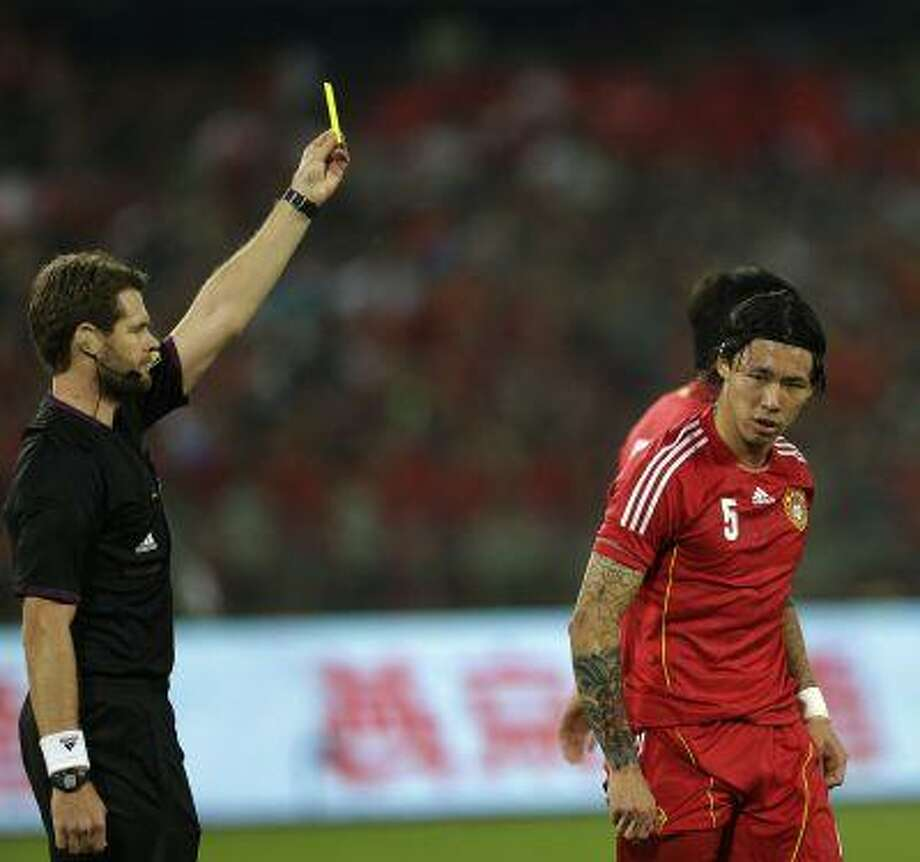 Referee Chris Beath shows a yellow card to China's Zhang Linpeng, right, during a friendly soccer match between China and Netherlands held at the Worker's Stadium in Beijing, China, Tuesday, June 11, 2013. Netherlands won 2-0. Photo: ASSOCIATED PRESS / AP2013
