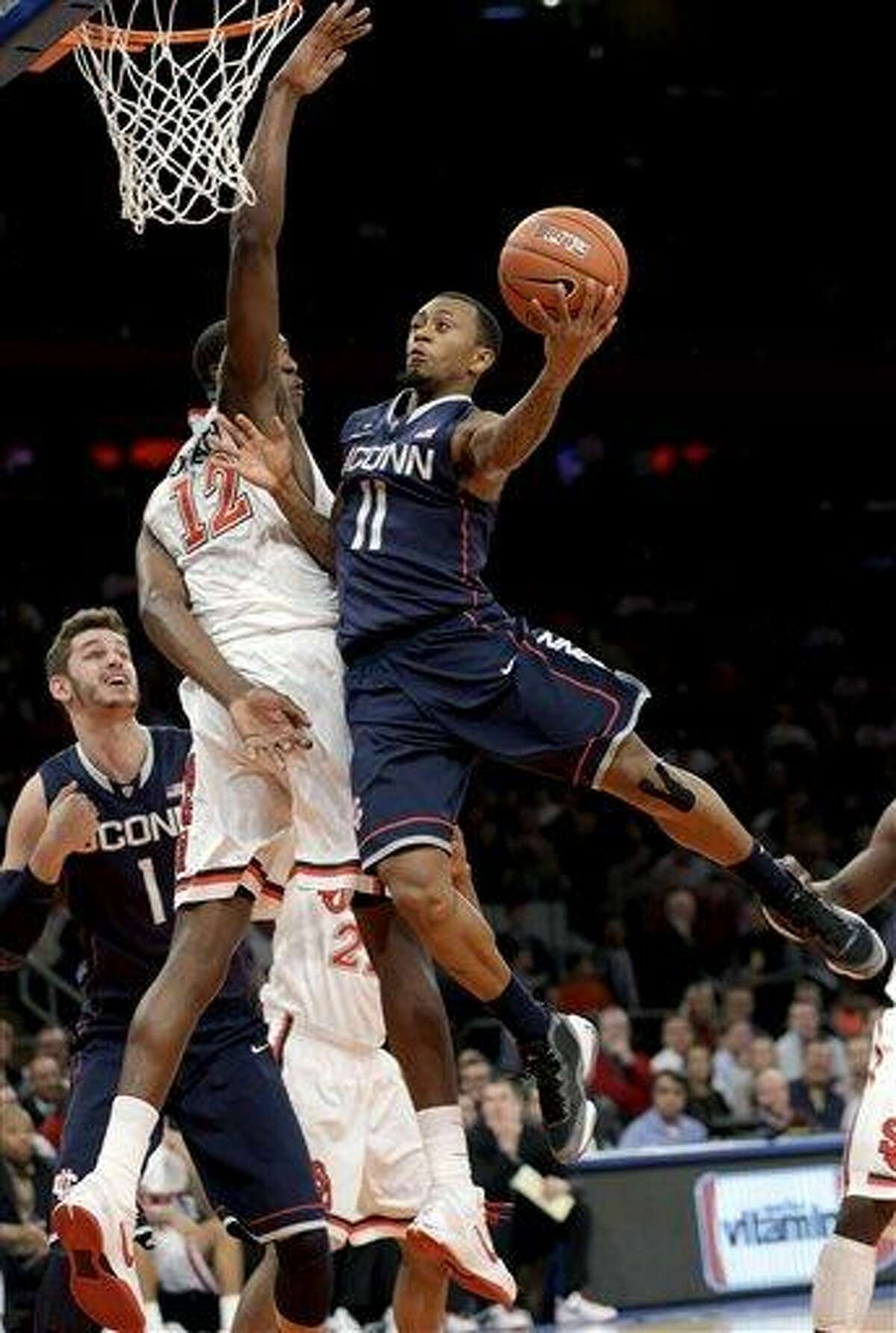 St. John's Chris Obekpa (12) defends as Connecticut guard Ryan Boatright (11) shoots a layup during the first half of their NCAA college basketball game, Wednesday, Feb. 6, 2013, at Madison Square Garden in New York. (AP Photo/Kathy Willens)