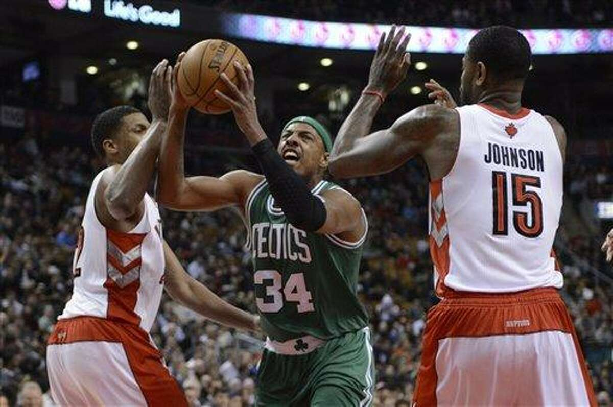 Boston Celtics forward Paul Pierce, center, drives to the basket as Toronto Raptors' Amir Johnson, right, and Rudy Gay defend during first-half NBA basketball game action in Toronto, Wednesday, Feb. 6, 2013. (AP Photo/The Canadian Press, Frank Gunn)