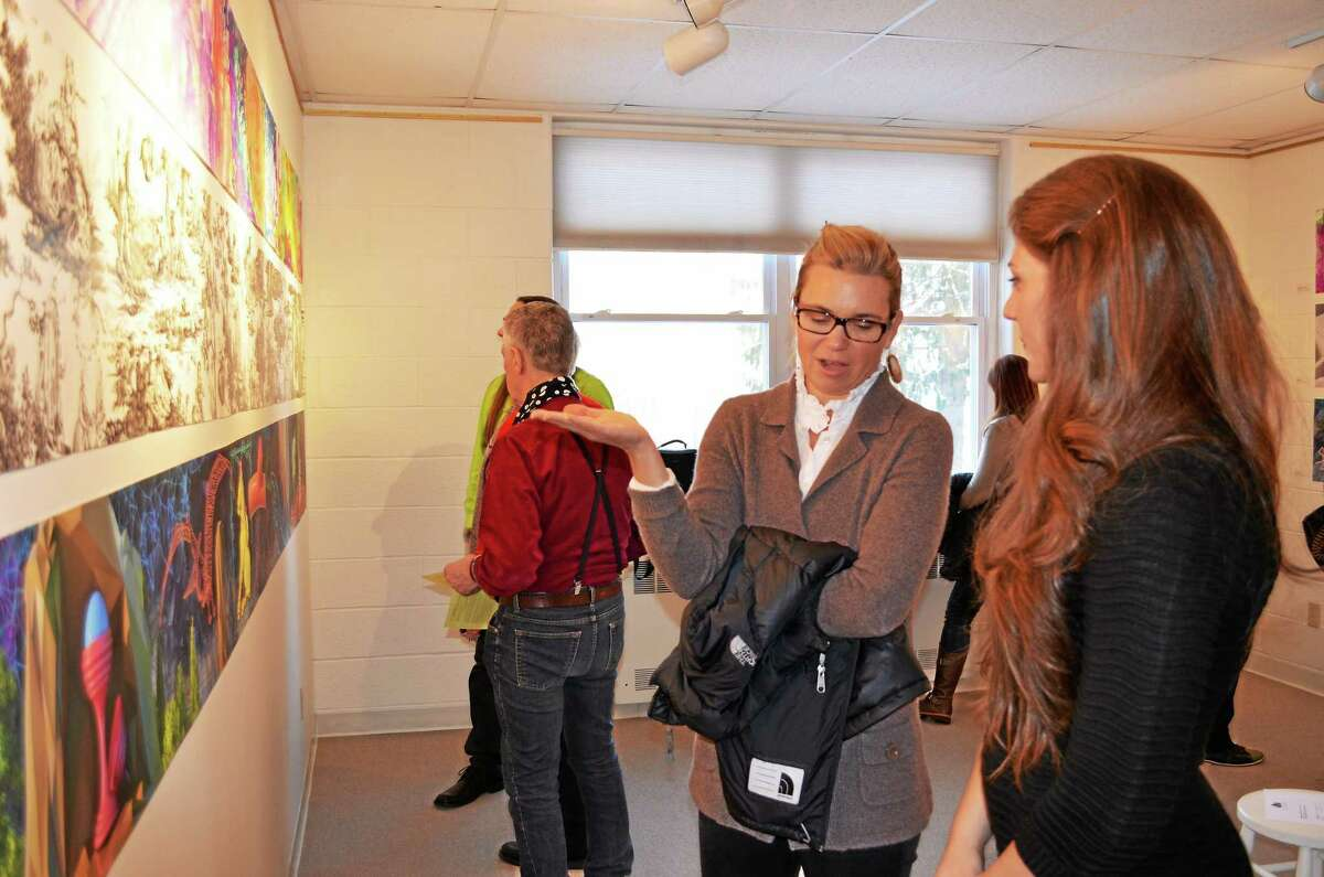 Artist Naya Bricher discusses her work in the collective exhibit Realms, which she created with her parents Mary Terrizzi and Scott Bricher, with a gallery visitor during the opening on Sunday.