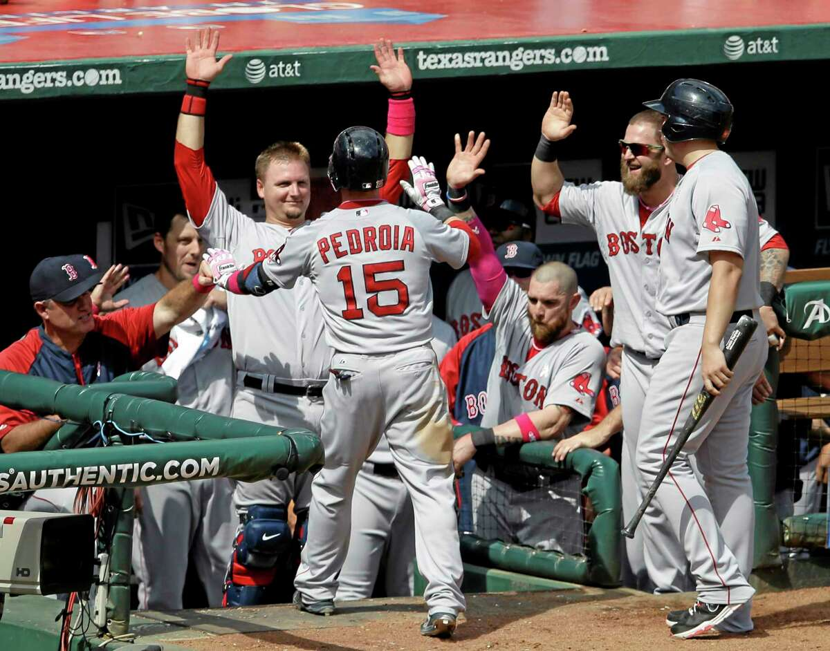 Dustin Pedroia (15) is congratulated at the top of the dugout by manager John Farrell, left, catcher A.J. Pierzynski and Mike Napoli, second from right, following his solo home run in the seventh inning Sunday.