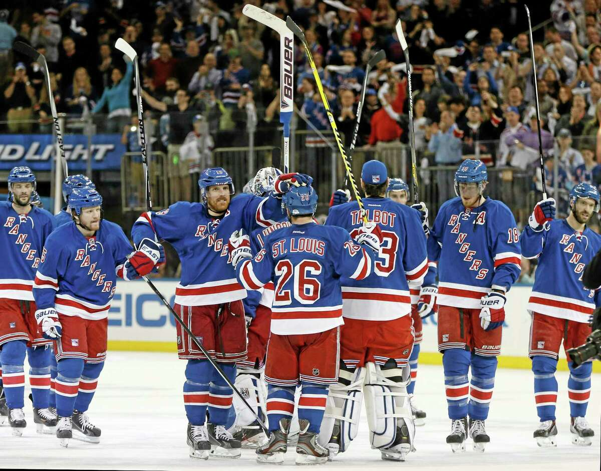 Rangers center Brad Richards (19) pats Rangers right wing Martin St. Louis (26) on the helmet as the Rangers celebrate their 3-1 win over the Penguins Sunday in game 6 of their playoff series.