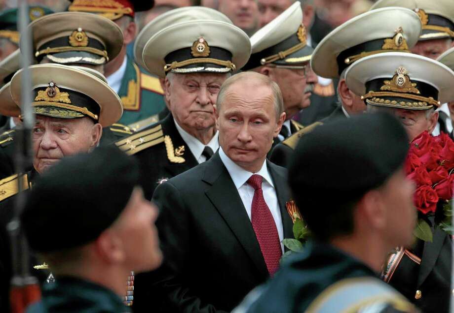"""Russian President Vladimir Putin attends a parade marking the Victory Day in Sevastopol, Crimea, Friday, May 9, 2014. Presiding over a triumphant spectacle of warships and fighter jets, Putin hailed the return of Crimea to Russia as the restoration of """"historic justice"""" before a jubilant, welcoming crowd Friday on the holiday that Russians hold dearest to their hearts. (AP Photo/Ivan Sekretarev) Photo: AP / AP"""