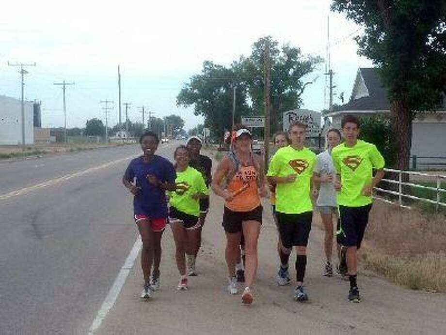Part of the Brush High School cross country team joins Amy VanDyke on running along state Highway 34 during her leg of the MS Run the US fundraiser, which passed through Brush Friday, June 14, 2013. VanDyke finished her run from Hudson to Wray a little before noon Monday, June 17. (Photo courtesy Jeff Marcus) / Fort Morgan Times