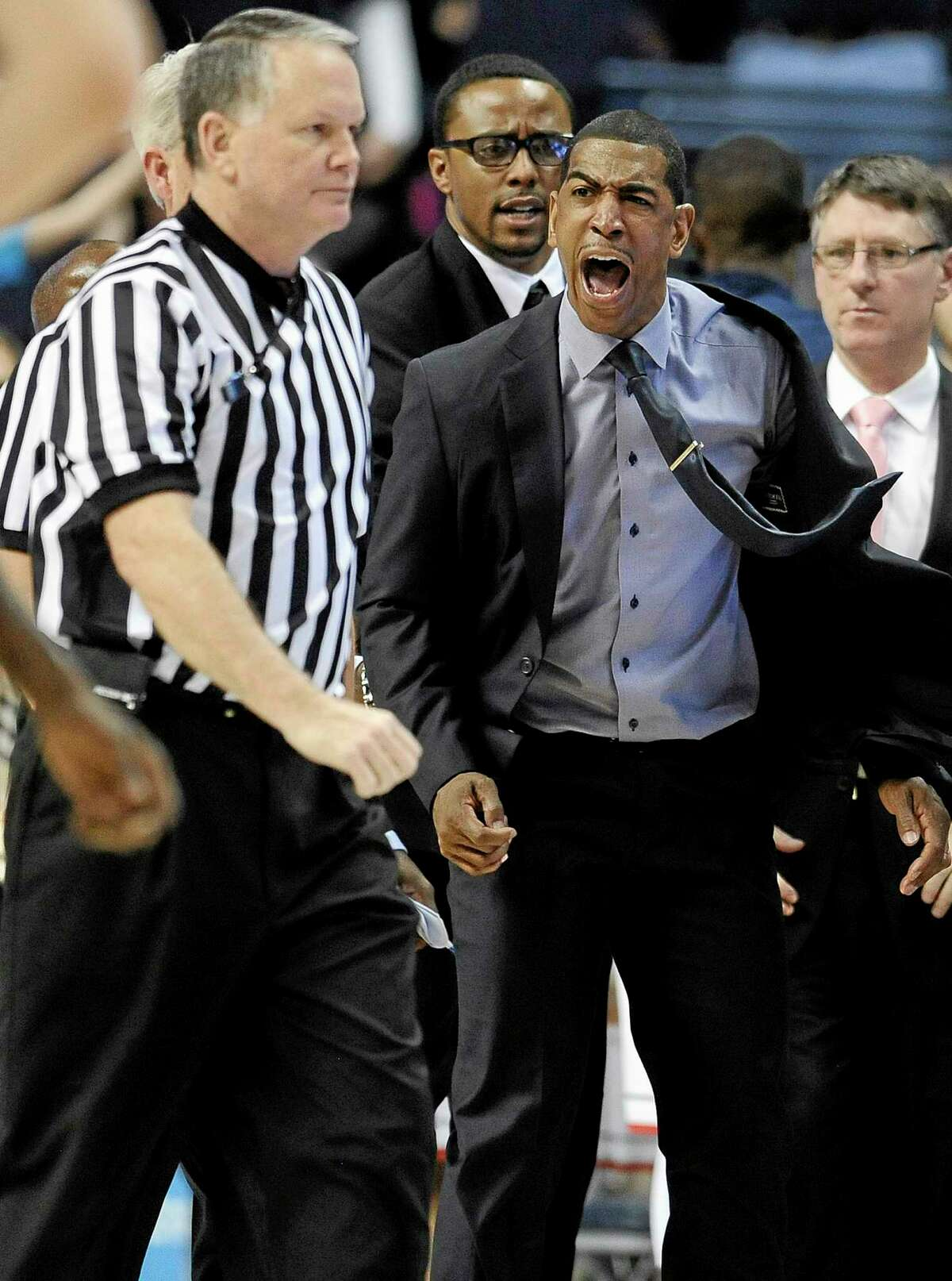 UConn coach Kevin Ollie, right, yells toward an official during the second half of Saturday's game against Louisville in Storrs. Ollie received two technicals on the play and was ejected from the game.
