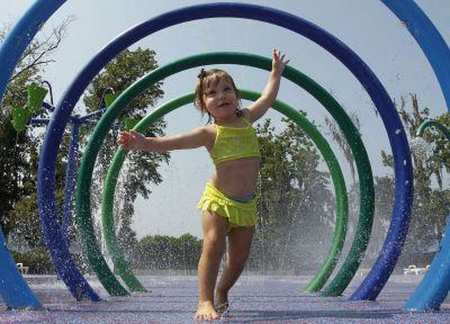 Alivia Parker, 21 months, runs through circles of spraying water on a 100 degree day in Montgomery, Ala., Tuesday, June 14, 2011. Parker is wearing sunscreen with an SPF of 100. (AP Photo/Dave Martin) Photo: ASSOCIATED PRESS / AP2011