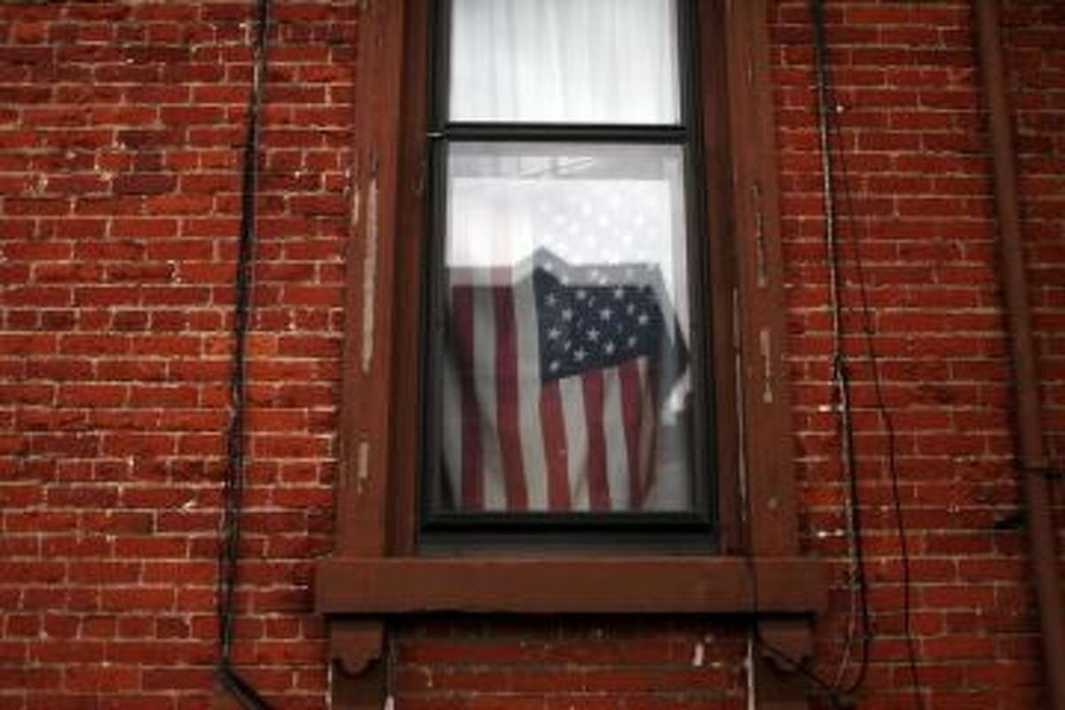 A flag hangs in a window in Utica, NY.