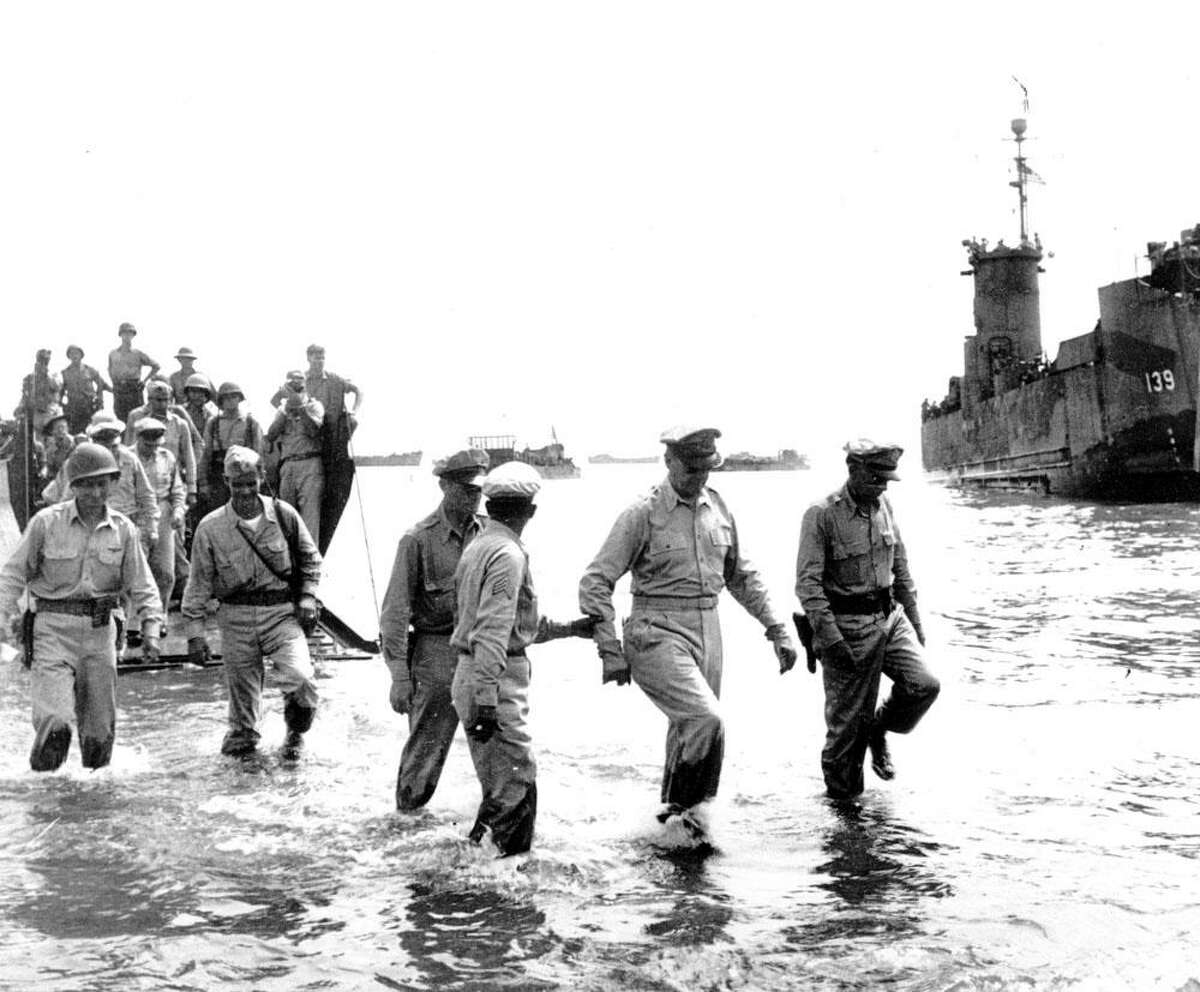 General Douglas MacArthur, front center, wades ashore with his Army as they arrive at Leyte Island in the Philippines on Oct. 20, 1944 during World War II. (AP Photo)HC00408