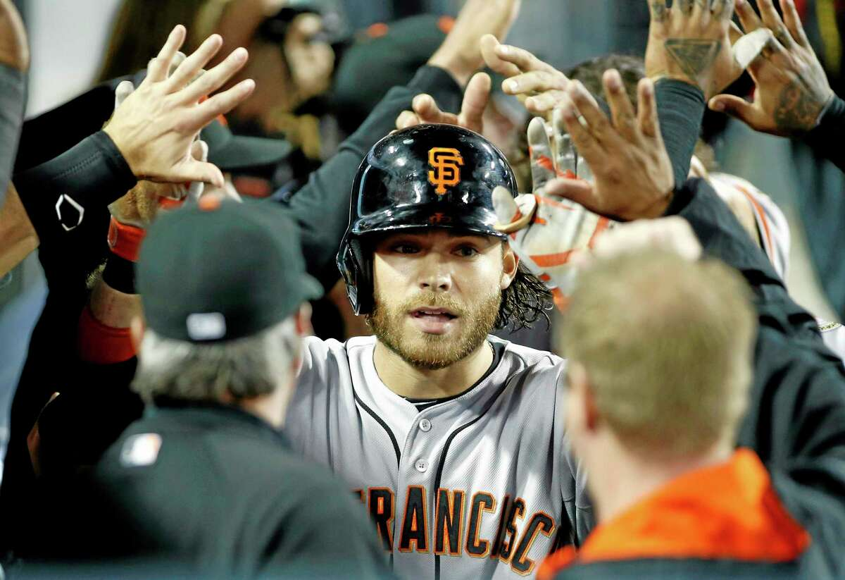 The San Francisco Giants' Brandon Crawford is congratulated in the dugout after hitting a two-run home run against the Dodgers on Friday in Los Angeles.