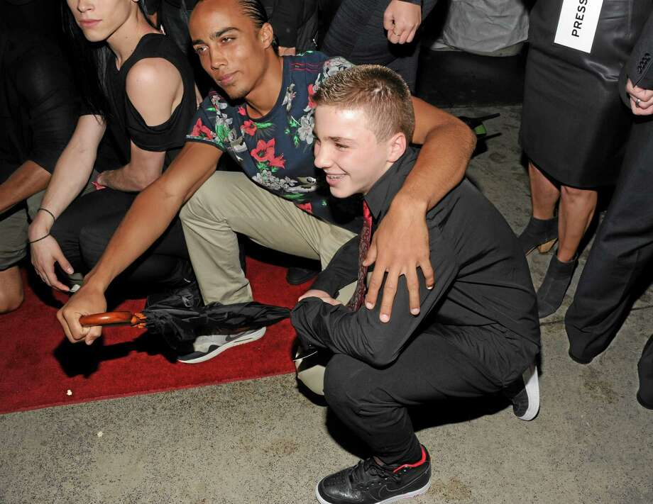 "FILE - In this Tuesday, June 18, 2013 file photo, Madonna's son, Rocco Ritchie, foreground, attends the world premiere of ""Madonna: The MDNA Tour"" at the Paris Theatre in New York. Madonna is apologizing for using a racial slur to refer to her white son Instagram. On Friday night, Jan. 17, 2014, she posted a picture of her 13-year-old son boxing and used a hashtag that contained a racial slur. When fans objected, she defiantly called them haters, but in a statement to The Associated Press on Saturday, Jan. 18, 2014, she was contrite and said: ""Forgive me."" (Photo by Evan Agostini/Invision/AP) Photo: Evan Agostini/Invision/AP / Invision"