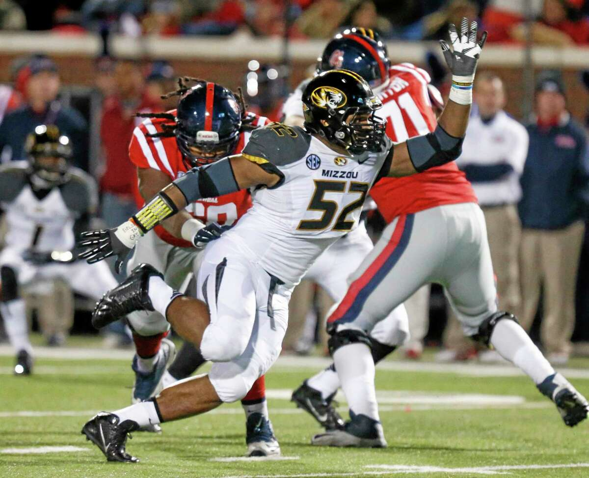 In this Nov. 23, 2013, file photo, Missouri defensive lineman Michael Sam pushes past a block by Mississippi lineman Pierce Burton during a game in Oxford, Miss.
