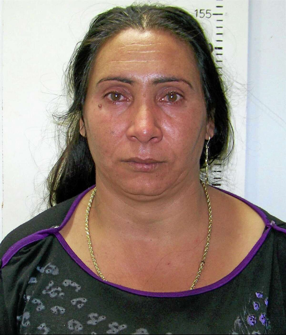 """In this police handout photo taken on Thursday , Oct. 17, 2013, Greek Roma, Eleftheria Dimopoulou, 40, or Selini Sali —a woman who has two separate sets of identity papers. is seen in the Larisa regional police headquarters, Greece. Dimopoulou and her companion have been charged with abducting a little girl found living with them in a Gypsy settlement. Police in Greece on Monday, Oct. 21, 2013, have released the photographs of a couple alleged adductors of a girl known """"Maria"""" after they were formally taken onto pre-trial custody and an international search for the girl's parents intensified. (AP Photo/Greek Police)"""