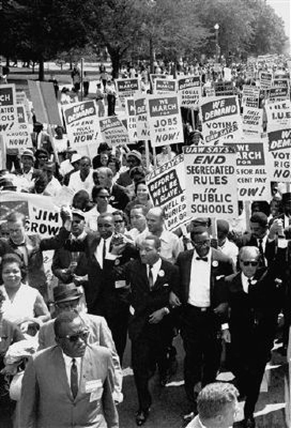 Martin Luther King, Jr., center front, marches for civil rights, arms linked in a line of men, in the Aug. 28, 1963, March on Washington.