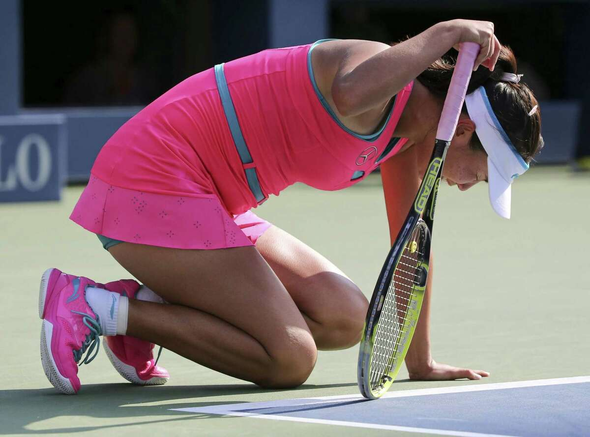 Peng Shuai drops to her knees in pain during the semifinals of the U.S. Open against Caroline Wozniacki on Friday in New York. Peng left the court in a wheelchair and retired from the game, forfeiting it to Wozniacki.