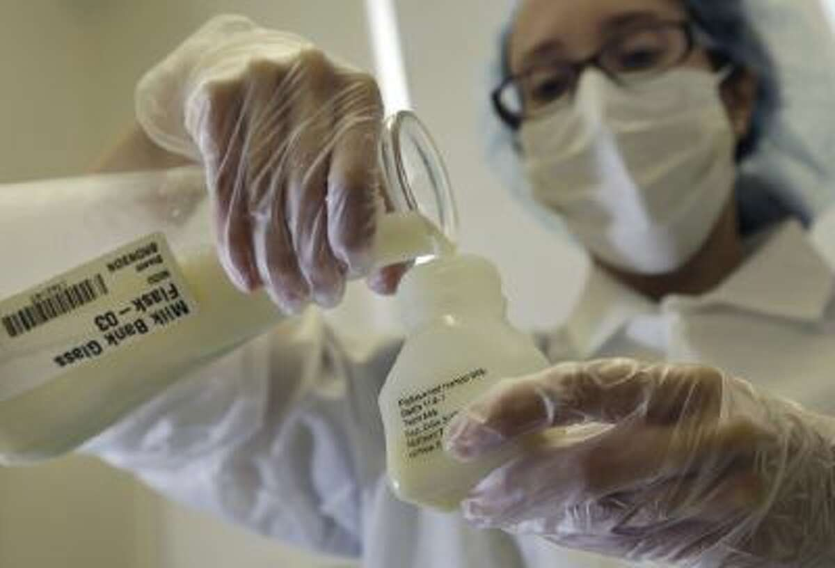 A lab technician pours donated breast milk into a plastic bottle for pasteurization.