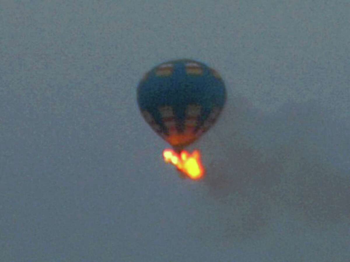 This photo provided by Nancy Johnson shows what authorities say is a hot-air balloon that wass believed to have caught fire and crashed in Virginia, Friday, May 10, 2014. Virginia State Police received calls of the crash shortly before 8 p.m., police spokeswoman Corinne Geller told a news conference. Geller said a pilot and two passengers were believed to be on board, and that police believe it was the gondola that caught fire. (AP Photo/Nancy Johnson)
