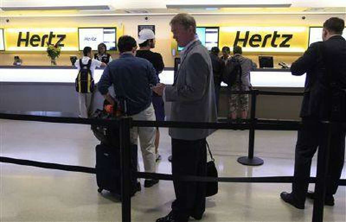This May 9, 2011 photo shows customers waiting in line at a Hertz rental car counter at San Jose International Airport in San Jose, Calif. Car rental agencies sometimes don't have enough cars to meet the demand. If there are no cars left at its airport rental facility, Hertz will let customers rent from a competitor and pay the difference, or pay for a cab to and from your hotel. (AP Photo/Paul Sakuma/file)