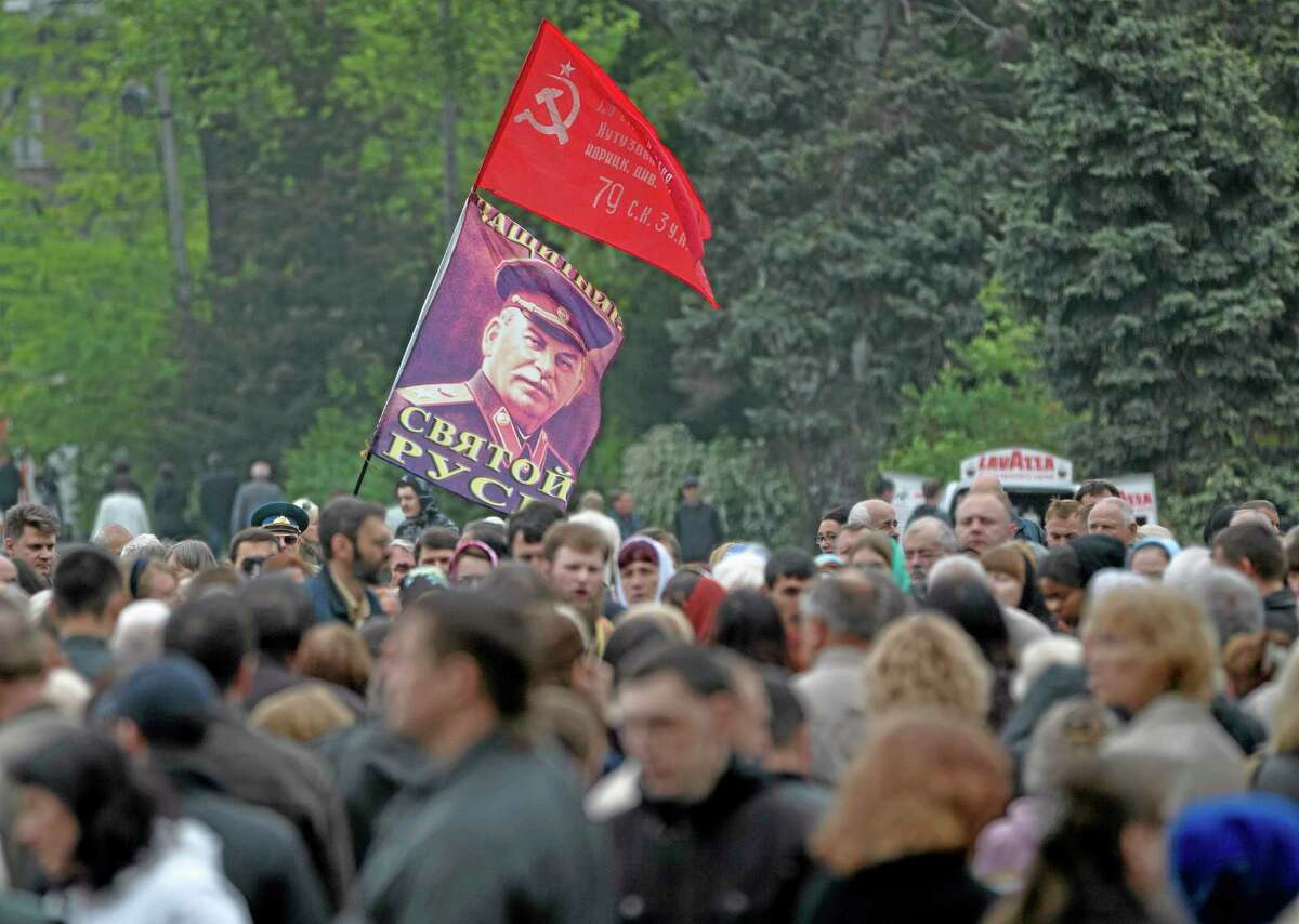 A WWII Soviet flag replica and a portrait of former Soviet leader Joseph Stalin fly above crowds gathered for a religious service in memory of the the victims of last week's trade union building blaze in Odessa, Ukraine, Saturday, May 10, 2014. The Black Sea port of Odessa was last week rocked by violent clashes between pro-Russian forces and supporters of the central government that left nearly 50 people dead. (AP Photo/Vadim Ghirda)