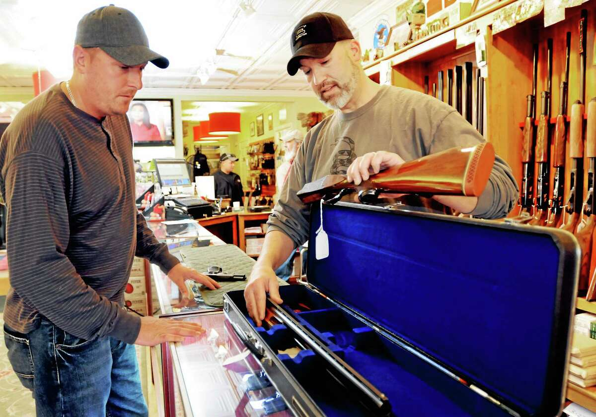 (Peter Hvizdak - New Haven Register) John Gray of East Haven, left, admires a competition Winchester 101 double-barreled shotgun Friday, May 9, 2014 shown by Mike Higgins, co-owner of TGS Outdoors gun shop in Branford.