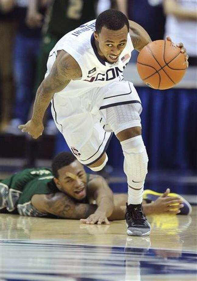 Connecticut's Ryan Boatright, foreground, drives past South Florida's Anthony Collins during the second half of an NCAA college basketball game in Storrs, Conn., Sunday, Feb. 3, 2013. Connecticut won the game in overtime 69-64. (AP Photo/Fred Beckham) Photo: ASSOCIATED PRESS / AP2013