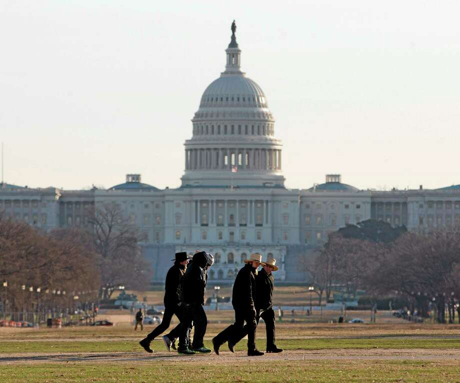 With the Capitol in the background, a group of men walk across the National Mall in Washington as they head toward the Smithsonian Museum, Tuesday, Jan. 7, 2014. Frigid air that snapped decades-old records will make venturing outside dangerous for a second straight day Tuesday, this time spreading to southern and eastern parts of the U.S. and keeping many schools and businesses shuttered. Residents driven from their homes by power outages in the Midwest longed to return to their own beds.(AP Photo/Pablo Martinez Monsivais) Photo: AP / AP
