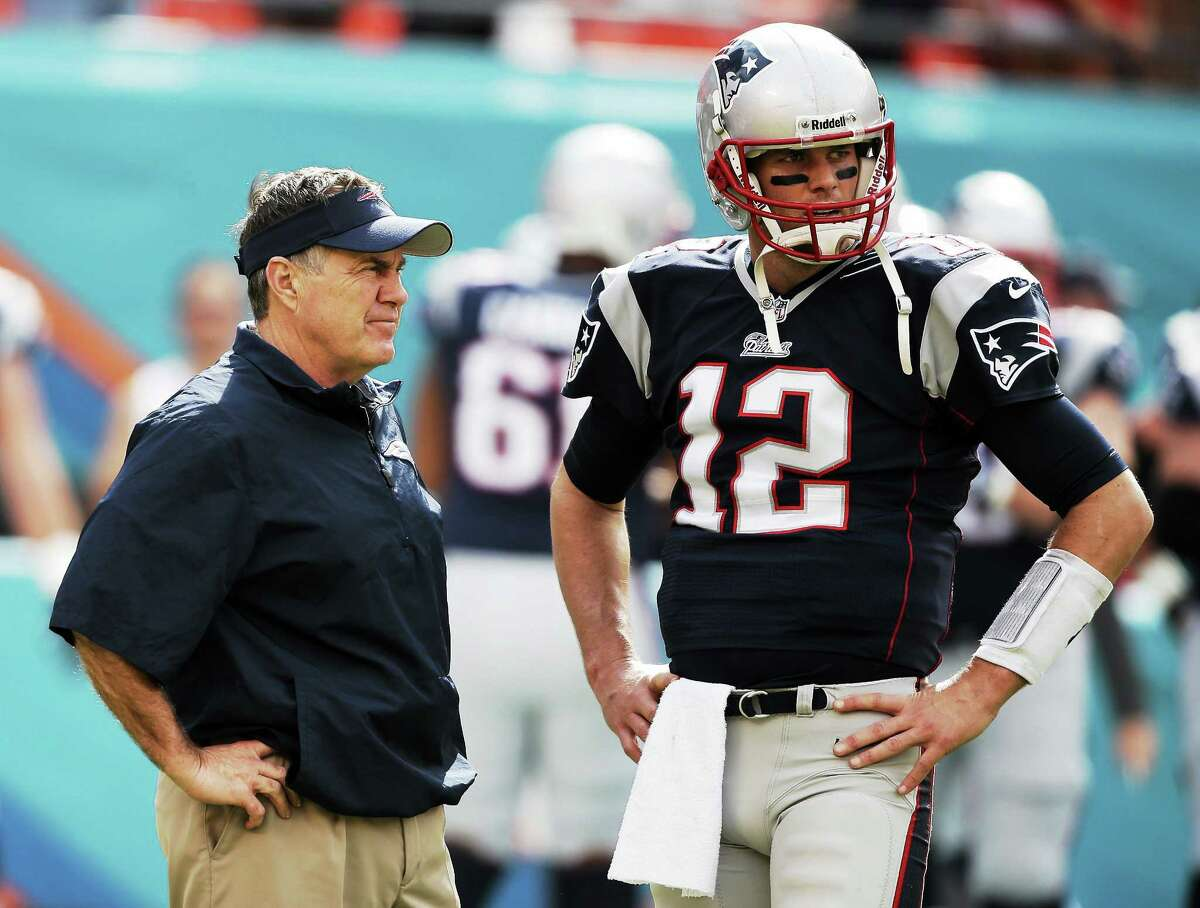 New England head coach Bill Belichick and quarterback Tom Brady talk on the sidelines before the Patriots' game at the Miami Dolphins on Dec. 15.