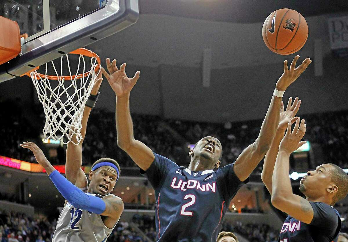UConn forward Deandre Daniels (2) and guard Omar Calhoun, right, fight for a rebound against Memphis forward David Pellom (12) during the second half of Thursday's win at Memphis. On Saturday night the Huskies welcome defending champion Louisville to Gampel Pavilion.
